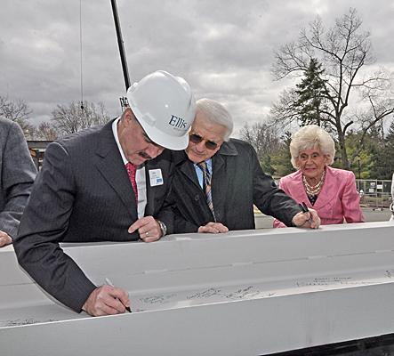 James Connolly, CEO of Ellis Medicine, signs a beam as part of a ceremony to kick off construction at Bellevue. Looking on are Neil Golub and Jane Golub of the Golub Corp., parent of the Price Chopper supermarket chain. A breast care and imaging center is named for the Golubs.