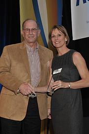 Michael Jacobson, executive director of Capital District Habitat for Humanity, receives the Non-Profit of the Year award from Business Review Publisher Carolyn M. Jones.