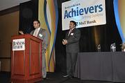 Brothers Vikash Agrawal (at the podium) and Vikram Agrawal receive the Newsmaker award at The Business Review's Achievers ceremony Nov. 10. Vikash is chairman; Vikram is president and CEO.