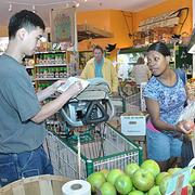 At the Honest Weight Food Co-op, Jiayuh and Tamirah Ju shop with their daughter Maia. The Co-op is still waiting for the financing it needs to open a larger store.