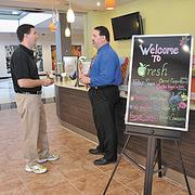 """Crossgates GM Joe Castaldo, right, speaks with Michael Gourlay, a Fresh Healthy Cafe franchisee. """"We're very happy with what we've seen,"""" Castaldo said of activity at the mall."""