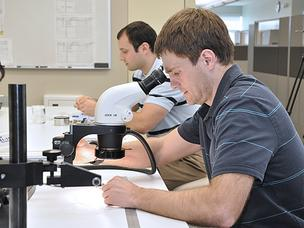 AngioDynamics engineers Dan Buehner, left, and Kevin Swift examine catheters at the company's Latham, New York research and development lab. A new federal tax could cost their company $6 million next year.