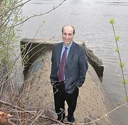 Rocco Ferraro, head of the Capital District Regional Planning Commission, stands on a pipe in Watervliet that spills untreated sewage into the Hudson River. The river's health has steadily improved over the past couple of decades. Ferraro's group led six years of sewer studies, one of the last outstanding aspects of the river's clean-up.