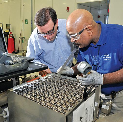 From left, Tim Baechle, operations leader, and Harold Narain examine a battery for a telecommunications customer.