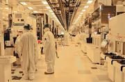 Engineers and technicians work on the manufacturing room floor at the GlobalFoundries plant in Malta.