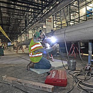 At peak, the building of the GlobalFoundries chip plant will require a construction work force of 1,600. Here, Carl Vallone performs a welding job at the site.