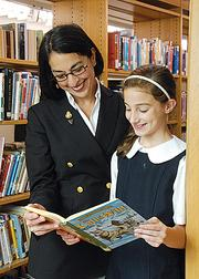 Academy of Holy Names President Eva Joseph reads with student Gillian Trimarchi in this file photo.