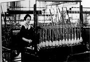 An unidentified employee from this 1920s photo works in a spooling area of the plant.