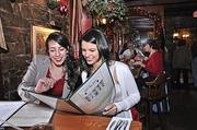 At The Olde Bryan Inn, Meghan Carroll, left, and Liz Rizzo look over the lunch menu. The restaurant offered coupons in the 2011 Entertainment Book, a yearly discount subscription publication.