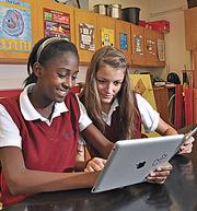 At Albany Academy for Girls, 8th graders Sabine Stain, left, and Allayla Silipigno work with iPads.