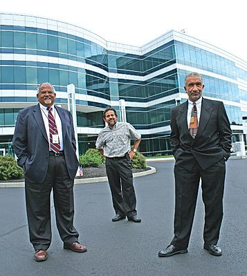 (From left) Ashok Sood, head of Magnolia Solar, which is adding jobs in Albany; Pradeep Haldar, vice president of clean energy programs at the College of Nanoscale Science and Engineering at UAlbany; and Alain Kaloyeros, CEO of CNSE. Here, the three stand in front of a building at the $7.5 billion complex.