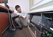 Mark Cambria, manager of the HVAC group at M/E Engineering, checks a unit ventilator at Union College's Lippman Hall.