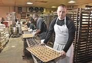 Next stop, the oven: Jeremy Williams, foreground, prepares a tray of miniature chocolate chip cookies for baking at The Cookie Factory in Troy.