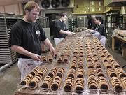 Joshua Maynard, an employee at The Cookie Factory in Troy, packages raspberry drop cookies at the company bakery.