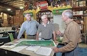Creatacor's VP of operations Gerald Glynn, left, VP of client services Will Farmer and senior account executive Richard Henaghan look over a display for LEGO.