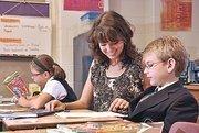 Doane Stuart School 3rd grade teacher Elizabeth Birkhead works with Ronan Costello, while Kira Nakushian reads. The school increased its financial aid budget this year.