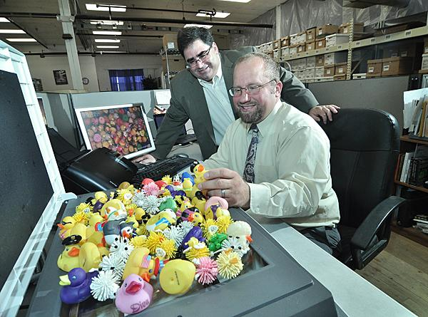 The Social Madness challenge has inspired companies to change the way they approach social media. Here, Howard Gross, left, president of E-BizDocs, and marketing manager Ben Dabrowski work on their Flatbed Fridays image—a creative series of photos posted online.