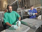 Employees John Baldwin, left, and Matt Huba in the processing area. Ecovative's mushroom technology is a replacement for Styrofoam packaging, and is being tested as filler for automobile doors, hoods and other parts.