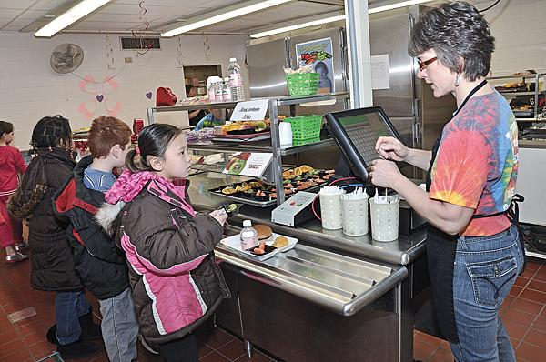 At Tesago Elementary School, part of the Shenendehowa Central School District, third-grader Shannon Waryncia pays cafeteria employee Wendy Schmaling for lunch.