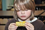 Leo Coons, a student at Tesago Elementary School in the Shenendehowa district, eats corn on the cob during a lunch break. New legislation requires schools to double the amount of fruits and vegetables they serve.