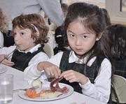 At Albany Academy for Girls, Ivyann Shen, foreground, eats a corned beef and cabbage lunch (with carrots). In the background is Nora Scheid.