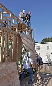 At the Alexander Street site in Albany, Habitat volunteers Brian Terbush, left, and Dennis Fitzgerald hoist a sheet of plywood to Habitat employees Frank Ranelli, left, and site supervisor Alphonso Gavin.