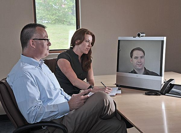 Kenneth Yanneck, CEO of IPLogic Inc. in Latham, said health care sales and a change in his corporate sales philosophy is driving revenue growth. Yanneck is seen here talking with Sandra Spinelli, the company's vertical development leader for health care and Svein Carlsen, a client support engineer who appears on the computer monitor.