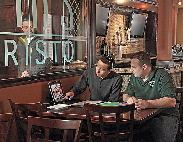 The new Appletini? Customers at the new Marotta's Bar-Risto in Schenectady will be able to order drinks and dinner on any of the 17 iPads. Above, left, Marotta's tech employee Joe Leverett tests the iPad system for restaurant owner Christopher Marotta.