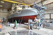 """At Scarano Boat Building, Mike McHale, left, and project manager Will Hempel, work on the Liberty V.  """"We're pushing our salaried guys as hard as we can,"""" says co-owner Richard Scarano."""