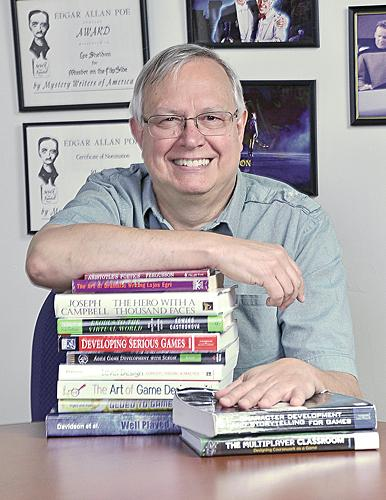 Lee Sheldon, associate professor and co-director of Rensselaer's Games and Simulation Arts and Sciences Program, is pictured with books he has written (at right) on video games.