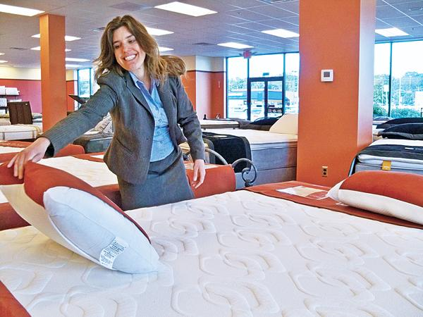 Chris Schorpp, showroom manager, fluffs a pillow at the new Sleepy's in Halfmoon. The mattress chain will open another store this summer less than a mile away in Clifton Park.