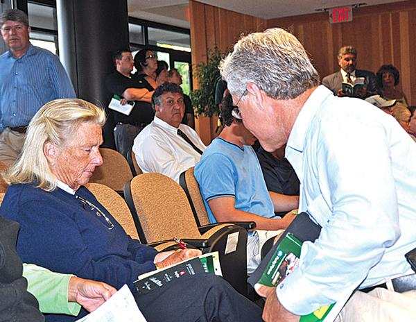 From left, Charlotte Weber signs for a horse she bought from Craig Bandoroff of Denali Stud.