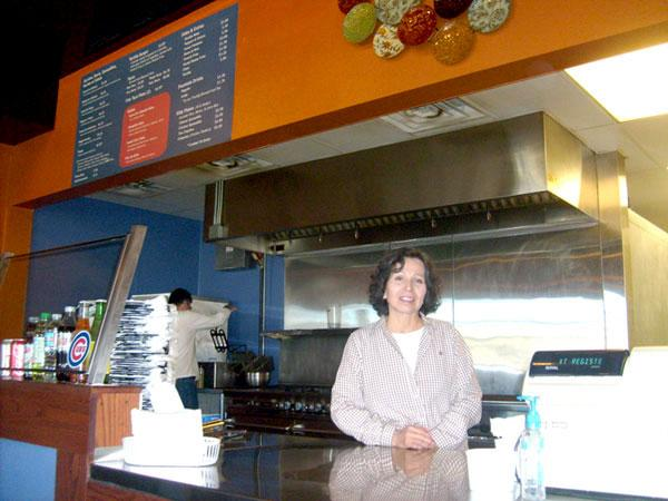 """Silvia (front) and Rubén Ceballos at Santa Fe Peppers. Customers choose ingredients for burritos and other Mexican dishes. A $5.95 """"everything burrito"""" weighs a full pound."""