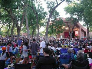 Crowds fill the park area for a Summer Concert series event at near the Rio Grande Zoo.