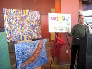 Artist Richard Gutierrez with his paintings