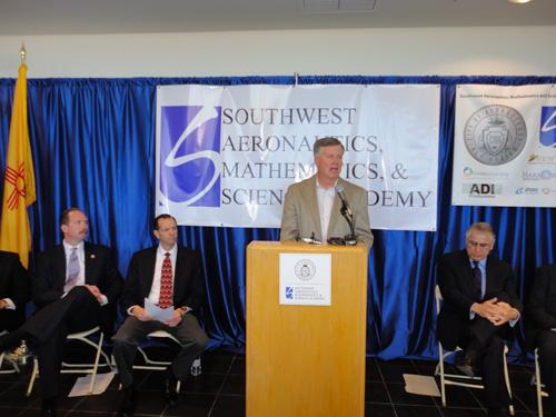 Aspen Avionics President and CEO John Uczekaj addresses attendees at a press conference announcing the charter school's lease with the city. Seated, from left, are Mayor Richard Berry, charter Founder and Head Administrator Scott Glasrud and former Democratic state Sen. Richard Romero.