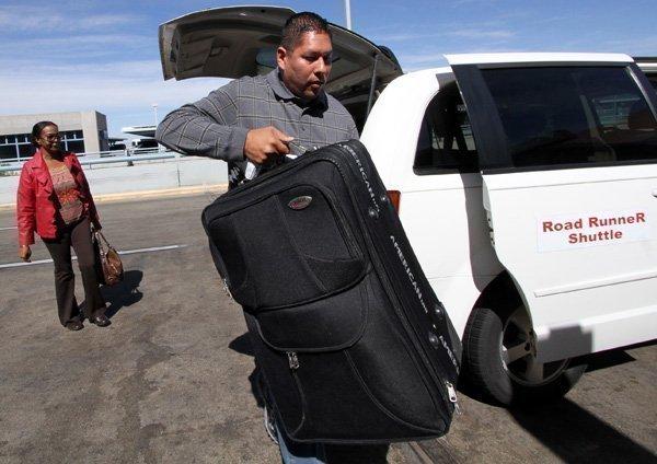 Roadrunner Shuttle Service driver Stephan Gross unloads luggage for Gloria Bias. Kathy and Mark Greenbury recently purchased Roadrunner Shuttle.