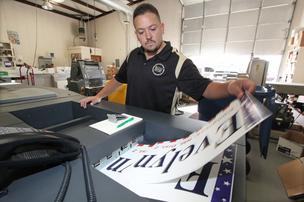 Craig Buster of printer First Impression Inc. works on campaign signs for a local candidate. Some printers say election ad spending is slow in New Mexico this year.
