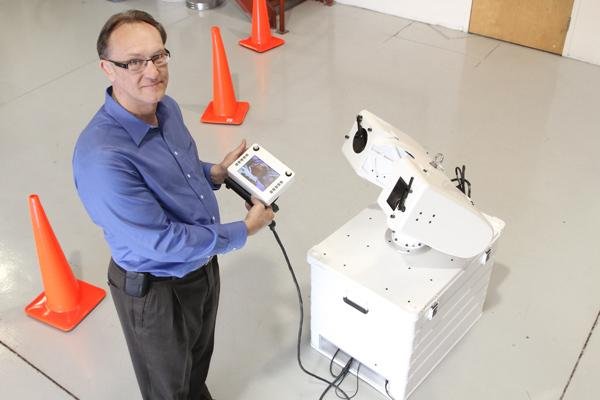 RIEtech Global President and CEO Rich Engstrom demonstrates how a surveillance system rotates on a gimbal developed by his company.