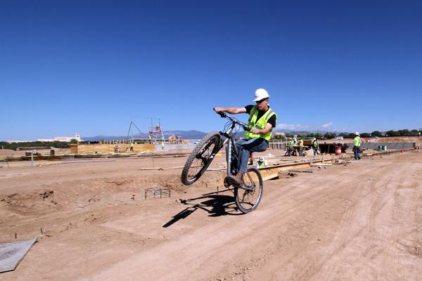 Bicycle Technologies Inc. Vice President Preston Martin rides his new bike at the company's new warehouse, which is under construction in Santa Fe.