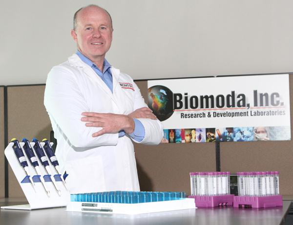 Biomoda CEO John Cousins with a tray of filters that aid in the detection of cancerous cells when used under a high-powered microscope.