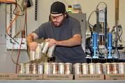 La Cumbre Brewing Co. intern Leo Dexter boxes up cans of the brewery's beer. In two years, La Cumbre has grown to 17 employees and produces 3,000 barrels of beer annually. But if the brewery hits 5,000 barrels, its excise taxes will jump.
