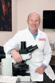 John Cousins with a high-powered microscope.