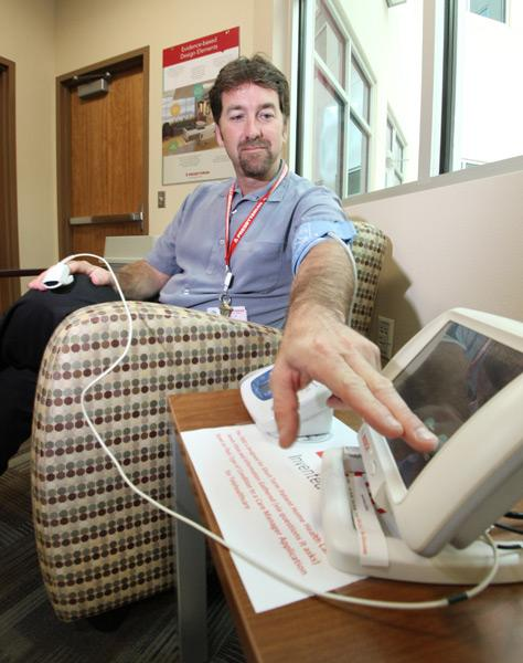 Presbyterian Director of Innovation/RN Doug Johnson demonstrates how a home health monitoring system works. The systems are likely to become more common in hospitals.