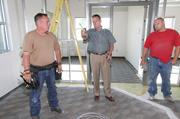 Ultramain President Mark McCausland (center) talks with Metro Electric electricians Patrick Roberts (left) and Dan DiNardo (right) at Ultramain's future office which is under construction.