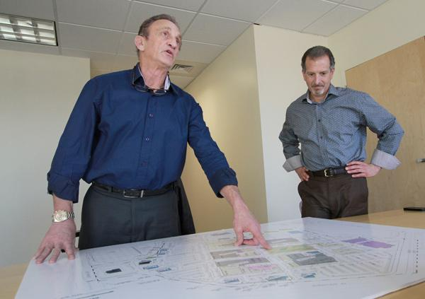 """Gary Goodman, left, and Darin Sand of Goodman Realty Group look at renderings for the Winrock Town Center development. Goodman calls Winrock a """"live, work, shop and play"""" community that will feature thousands of residential units, a full-service hotel and a large office component, including executive suites. Goodman aims to make every aspect of Winrock environmentally sustainable."""
