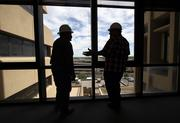 Klinger Project Supervisor Eli Gonzales, left, and Superintendent Carson Templeton talk on the bridge that will be removed from between the PNM buildings.