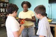 6th grade science teacher Beverly Miller helps students.