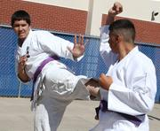 Sixteen-year-old Alexis Valdez, left, and Isziah Zuni, 15, demonstrate some of the moves they've learned in a karate class, part of the Albuquerque Institute for Mathematics and Science's physical education program.