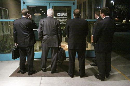 Five FDIC workers wait for someone inside to unlock the doors of First Community Bank's Albuquerque headquarters office at 6 p.m. on Jan. 28 so they can enter to do their jobs.